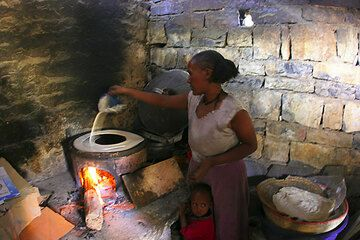 Eine Frau in ihrer dunklen kleinen Küche mit ihrem kleinen Kind zu Füßen zeigt uns, wie sie Injera macht - Injera, der Geschmack Ethiopiens und eine schöne Erinnerung. (c)