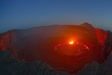 Lava lake after sunset; the glow of the lava illuminates the crater walls. Observers are visible as tiny silhouettes on the opposite crater rim. (Photo: Tom Pfeiffer)
