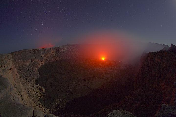 Glühen eines aktiven Hornitos im Südkrater und der Schein des Lavasees im Hintergrund bei Vollmond (Photo: Tom Pfeiffer)