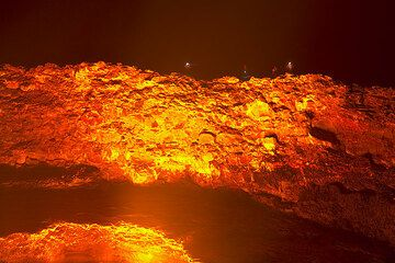 The group on the rim of the crater, whose walls are illuminated bright yellow and orange by the fountaining. (Photo: Tom Pfeiffer)