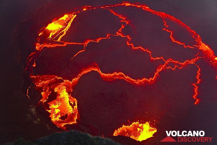 Vertical view onto the lava lake in the evening showing a typical scene of activity: 3 areas at the lake shore are moderately fountaining and several rifts occur on the surface of the lake, driven by internal convection of the magma. (Photo: Tom Pfeiffer)