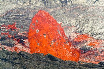 Eine Lavablase, die noch ihre Form beibehält, in vollem Sonnenlicht. Die Oberfläche des Lavasees im Hintergrund ist von Hitzeflimmern verwischt. (Photo: Tom Pfeiffer)