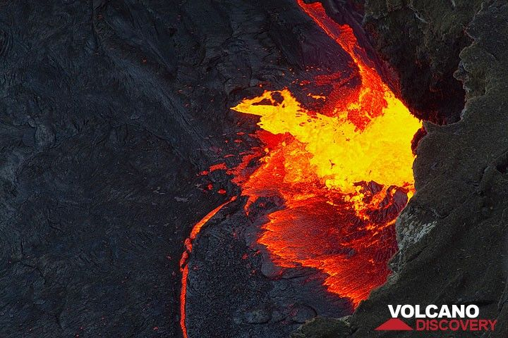 Fresh lava is sloshing out of the fountain onto the lava lake's crust, where a small crack is widening into a a tiny rift. (Photo: Tom Pfeiffer)