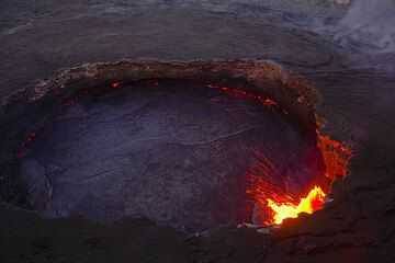 """The lava lake in the evening; its crust is quite solid there's almost no """"tectonic"""" movements (for the time being). Only the fountain at the western shore is very active. (Photo: Tom Pfeiffer)"""