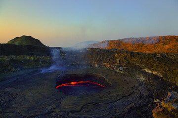 The morning sun illuminates the caldera walls orange. (Photo: Tom Pfeiffer)