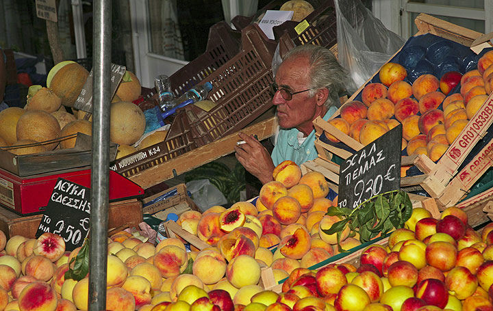 Fruit seller behind a tray full of ripe peaches (c)