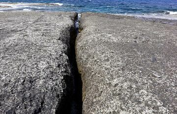 Wave erosion has cut out a narrow fissure through the ash deposit. With time, this widens into a channel. (Photo: Tom Pfeiffer)