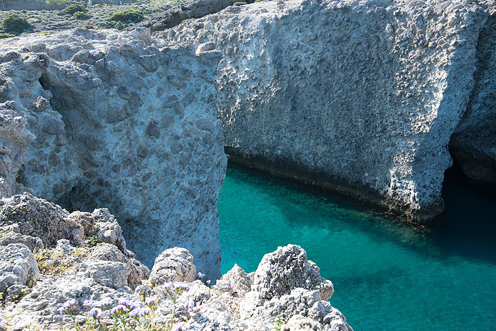 At Papafrankos, northern coast of Milos. Sea erosion has sculptured the spectacular pumice breccia into cliffs and caves. (Photo: Tom Pfeiffer)
