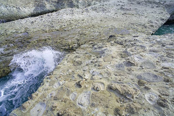 Large pumice stones embedded in the ash flow deposit, forming an arc over the water. (Photo: Tom Pfeiffer)