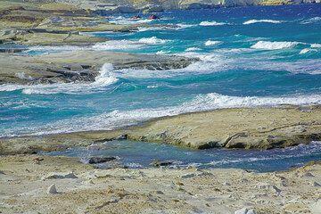 Die Nordküste von Milos bietet eines der geologischen Wunder der Erde: um die beliebte Sarakinikos Bucht herum stehen mächtie alte alte Ablagerungen von Aschen- und Bimssteinströmen an, die vom Meer zu strahlend weißen Formen und zerfurchten Klippen poliert wurden.  Normalerweise ein herrliches Gebiet zum Baden in den warmen Monaten zeigt Sarakinikos sich bei Wind und Wellen von einer rauen Schönheit, die man auf einer Wanderung entlang der Küste erleben kann. Dies sollte man sich bei einem Besuch der Insel wirklich nicht entgehen lassen! (Photo: Tom Pfeiffer)