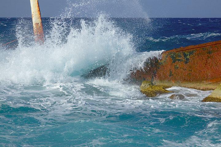 Powerful wave crashing over the shipwreck (Photo: Tom Pfeiffer)