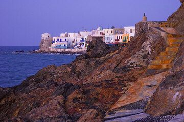 Waterfront of Mandraki after sunset. Colored volcanic rocks in the foreground. (c)
