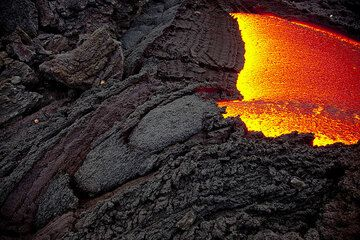 The lava flow emerging from its tube. Caused by friction and the sudden contact with cold air, successive segments of crust form at the exit, resulting in a progressive downstream growth of the tube's roof. (Photo: Tom Pfeiffer)