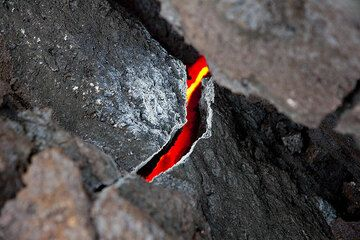 Escaping hot gasses from the hot interior of the flow react with the lava and leave white deposits.  (Photo: Tom Pfeiffer)