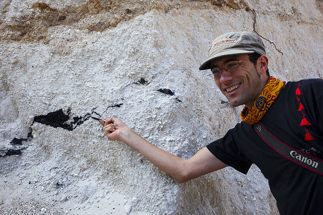 Yashmin explaining the charred wood found in the ignimbrite (ash flow) deposit. (Photo: Tom Pfeiffer)