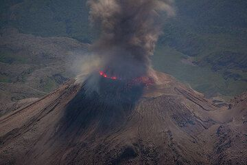 Ash eruption from the Santiaguito lava dome. Bluish flames around the circular perimeter of the active dome, corresponding to the outline of the vent, are visible.  (Photo: Tom Pfeiffer)