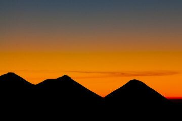 The silhouettes of Acatenango, Fuego and Atitlán volcanoes at dawn (Photo: Tom Pfeiffer)