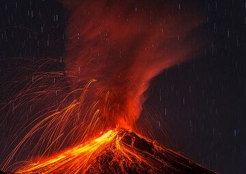 A powerful explosion showers the upper cone with glowing lava bombs, generating abundant avalanches and an ash plume. (Photo: Tom Pfeiffer)