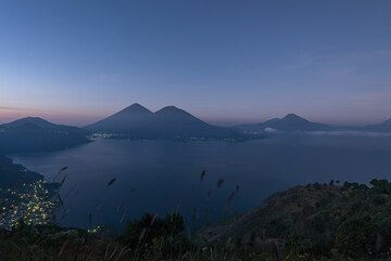 Early dawn view over the eastern part of Lake Atitlán with the lights of San Lucas Tolimán in the lower left. The pair of Atitlán (l) and Toliman (r) stratovolcanoes and the smaller San Pedro volcano (r) are opposite. (Photo: Tom Pfeiffer)