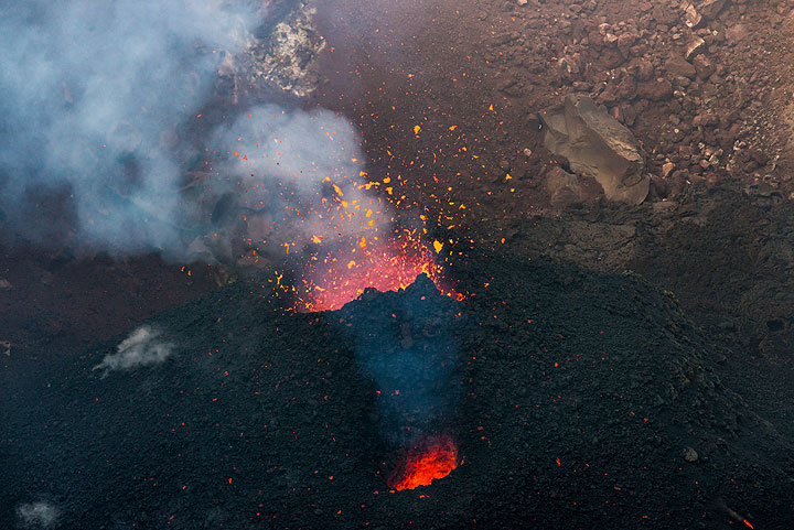 A secondary vent, a smaller glowing degassing hole, is present on the southeastern flank of the intra-crater cinder cone. Only occasionally, it also ejects spatter. (Photo: Tom Pfeiffer)