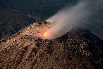 During one of the occasional stronger degassing phases which lasted up to 10-15 minutes, a loud jet-engine sound accompanies the stream of escaping hot gasses, and some small incandescent fragments and fine ash, from a fissure-like structure on the northeastern part of the crater floor. (Photo: Tom Pfeiffer)