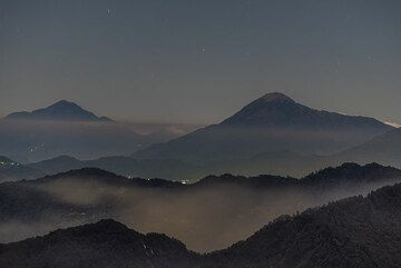View towards the western part of Guatemala's volcanic front with the silhouettes of Tacana (left background), at the border with Mexico, and Tacomulco volcano (right), where a light from a mountain camp is visible. (Photo: Tom Pfeiffer)