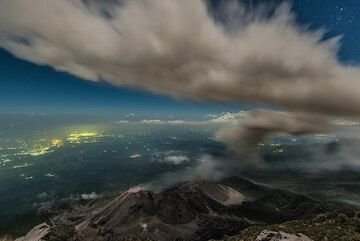 The ash plume from the first eruption is now high above our viewpoint (3600 m a.s.l.) and spreads laterally E-W. Later, fine ash fall on our camp terminates a cold and windy night's of observation. (Photo: Tom Pfeiffer)