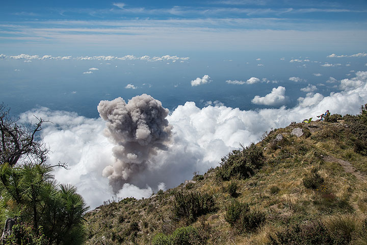 Another eruption in the afternoon sends an ash plume through the cloud deck covering the dome complex. (Photo: Tom Pfeiffer)