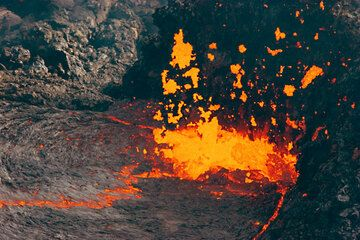 Schlackenauswurf von einer Bocca im östlichen Teil des Pu'u 'O' Kraters. Nachdem der Hornito über der Bocca während der Beobachtungen einstürzte, wurde der Blick auf die kochende Lava frei. (Photo: Tom Pfeiffer)