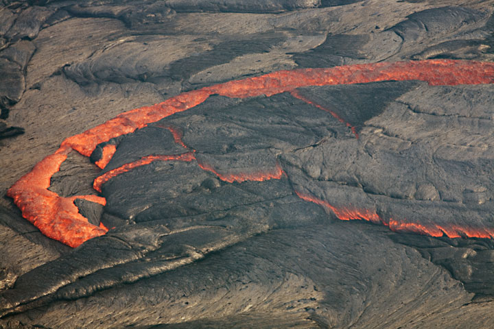 Overturning of older crust is a common feature at lava lakes. When the crust cools sufficiently, it contracts and becomes denser than the liquid underneath. Eventually, pieces of it become unstable and overturn to sink back into the lake. New crust is formed by upwelling lava from underneath. hawaii_e6829.jpg (Photo: Tom Pfeiffer)