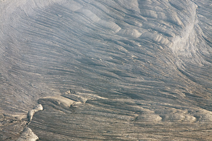 Silvery, ropy stripes record the initial streching the thin crust of the lava lake has undergone immediately before cooling sufficiently to become locally rigid. hawaii_e6842.jpg (Photo: Tom Pfeiffer)