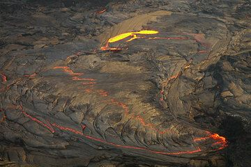 The lava lake in the evening light. At the far end, an overturn of crust has just taken place. (Photo: Tom Pfeiffer)