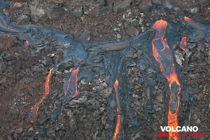 Two of the active vents (upper right) and several lava flows covering the older wall of the pit crater. (c)