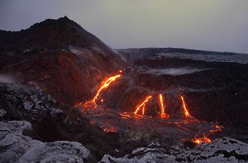 Perlenschnurartig angeordnete effusive Bocchen, aus denen Lavaströme in den Kollapskrater Puka Nui am Pu'u 'O'o Krater des Kilauea Vulkans auf Hawaii strömen. hawaii_e7579.jpg (Photo: Tom Pfeiffer)
