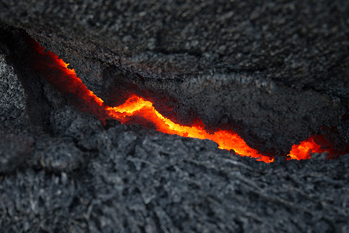 The incandescent lava is visible through cracks of the already cooled crust of the lava flow. (Photo: Tom Pfeiffer)