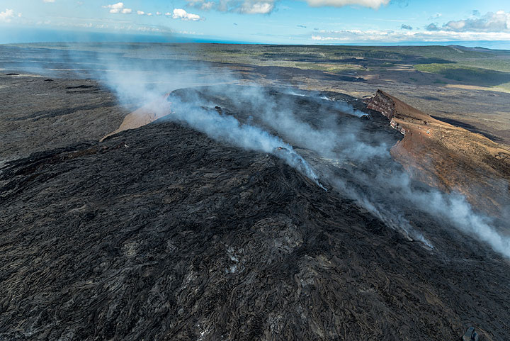 With time, lava has continued to fill the Pu'u 'O'o crater, overspilling large parts of the eastern (foreground) and western (background) rims. Gasses escaping from the vents feeding the active Kahauale'a lava flows to the lower right. (Photo: Tom Pfeiffer)