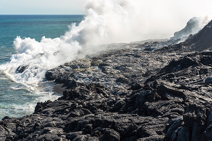 Within only 2 months, a significant, approx. 50 m wide bench of new land has been created. The feeding lava tube is located beneath the area with the bluish fumes in the right background at the older cliff. (Photo: Tom Pfeiffer)