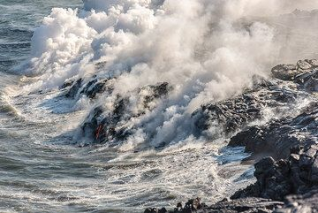 Tons of sea water are evaporated into acid steam as waves wash over the newly born, still hot land, hiding the view onto the red lava most of the time. (Photo: Tom Pfeiffer)