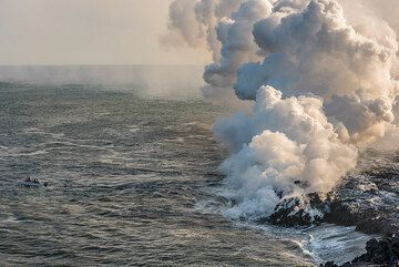 """As it gets evening, visitors come by boat to see the """"lava show"""". (Photo: Tom Pfeiffer)"""