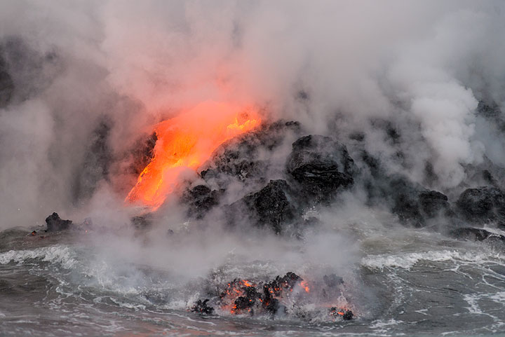 Floating lava pieces still glowing in the sea after being detached from the flow by the force of a wave. (Photo: Tom Pfeiffer)