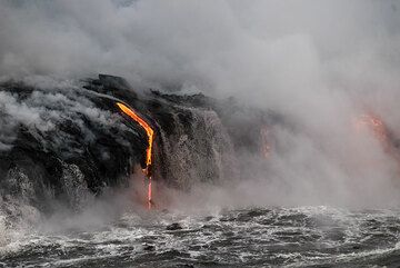As soon as the wave retreat, new streams of lava drop down from the small lava tubes feeding the sea entry. (Photo: Tom Pfeiffer)