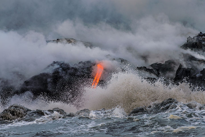 Fight of elements - a single lava flow tried to create land while the waves eat at it. Hot steam rises from the unstable bench of new land which is only few hours old. (Photo: Tom Pfeiffer)