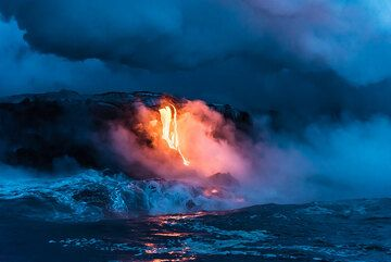 A lava entry forms a bright contrast to the blue hour light. (Photo: Tom Pfeiffer)