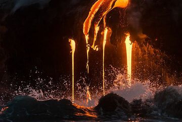 Small breaking wave in front of the lava hoses. (Photo: Tom Pfeiffer)