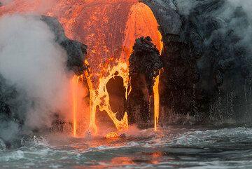 A flat sheet of liquid lava drops, forming Pele's Hair as the viscous liquid is torn into thin threads. (Photo: Tom Pfeiffer)