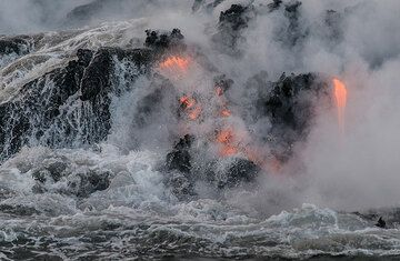 Lava, still glowing and cooled down is washed by a wave. (Photo: Tom Pfeiffer)