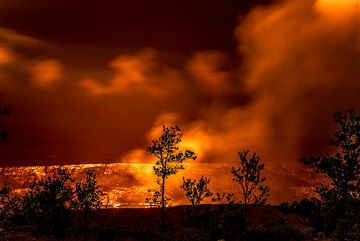 Small ohia trees form silhouettes against the red glow from the lava lake. (Photo: Tom Pfeiffer)