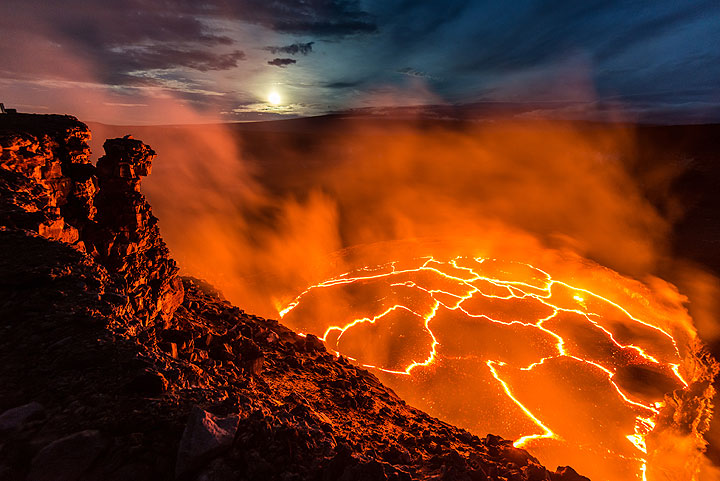 The lava lake and the moon setting above the distant silhouette of Mauna Loa shield volcano. (Photo: Tom Pfeiffer)