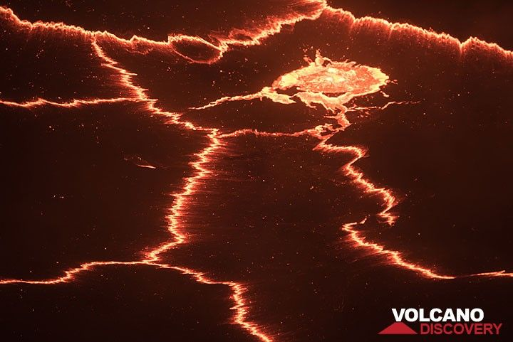 """Small degassing fountain makes a """"hole"""" into the crust of the lava lake. (Photo: Tom Pfeiffer)"""