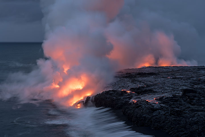 The lava glow becomes weaker as the daylight becomes stronger. A surface flow in the lower right center part is approaching slowly the cliff of the bench. (Photo: Tom Pfeiffer)